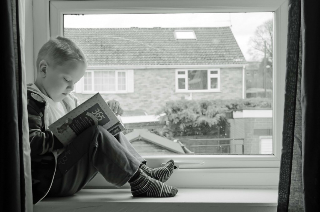 boy sitting on windowsill reading